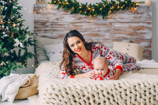Happy mom with her little daughter in holiday clothing with printed deers and snowflakes having fun on the bed in cozy room with a christmas tree and christmas lights. new year and christmas concept.