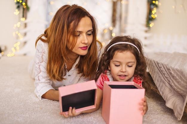 Счастливая мама с ребенком, глядя внутрь рождественской подарочной коробке