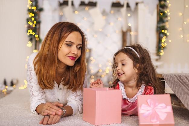 Счастливая мама с ребенком, глядя внутрь волшебной рождественской подарочной коробке