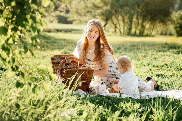 Happy mom with little daughter sits on a green lawn in the park on a picnic with baskets family day of parents with children