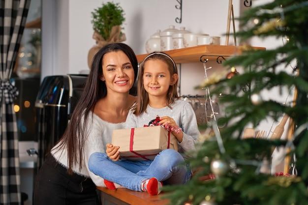 Счастливая мама с маленькой дочкой, получившей рождественский подарок от санты