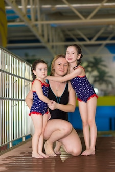Happy mom with little daughters in identical swimsuits posing on the bridge in the water park