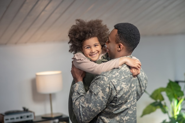 Happy moment. african woman american little girl in arms of military man standing happy emotional at home in room
