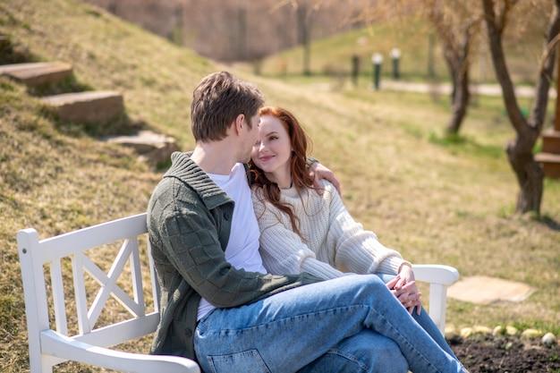 幸せな瞬間。自然の中でベンチに座ってお互いを見ている幸せな生姜髪のきれいな女性と抱きしめる男