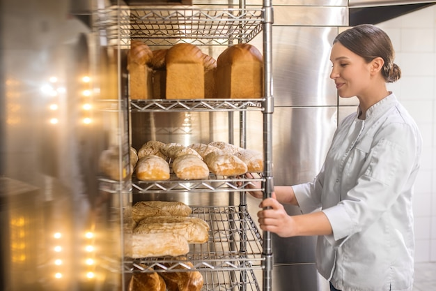 행복한 순간. 갓 구운 빵에 감탄과 함께 찾고 베이커리 카운터 근처에 서 행복 젊은 성인 여자