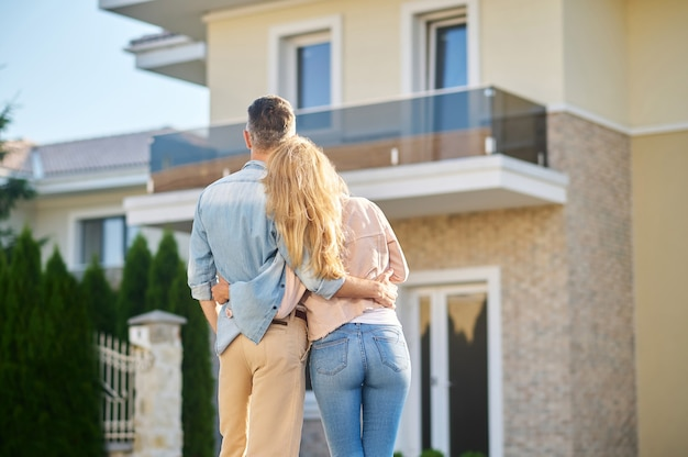 Happy moment. rear view of man and long-haired woman in casual clothes looking at their new home on fine afternoon