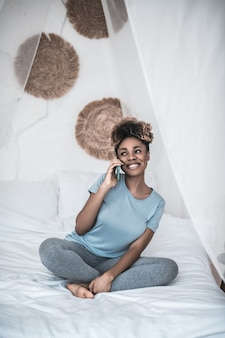 Happy moment. shining happy black woman barefoot talking on smartphone sitting on bed in light bedroom