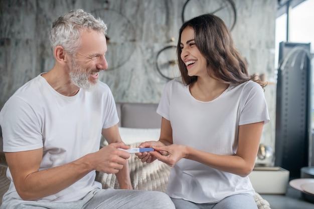 Счастливый момент. сияющие радуются возбужденные седые бородатые муж и жена с длинными темными волосами с тестом на беременность