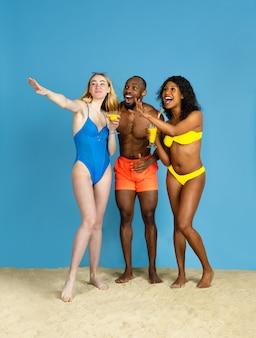 Momenti felici. giovani amici felici che riposano e che si divertono su sfondo blu studio. concetto di emozioni umane, espressione facciale, vacanze estive o fine settimana. freddo, estate, mare, oceano.