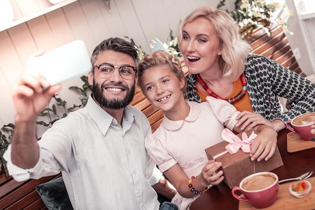 좋은 순간들. 자신의 사진을 찍는 동안 카메라를 찾고 즐거운 행복한 가족