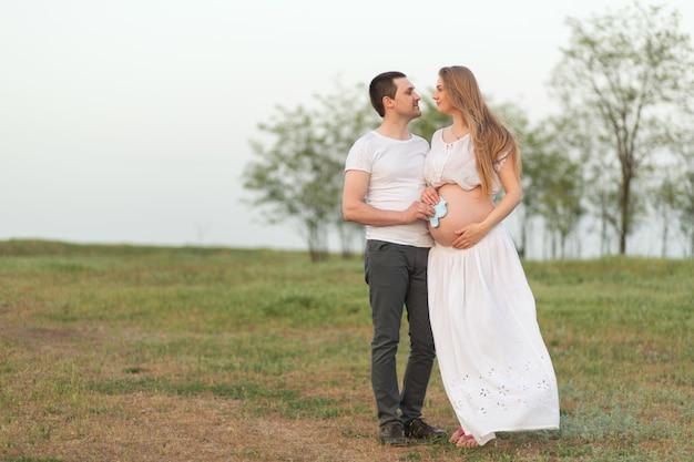 임신의 행복한 순간. 도시에서 멀리 떨어진 신선한 공기를 마시 며 임신 한 아내와 함께 사랑하는 남편.