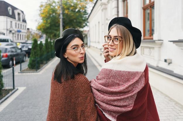 2人のスタイリッシュな女の子との幸せな瞬間、肩越しに見て、笑顔で、街の通りを歩いています。クローズアップの肖像画、面白くて楽しい魅力的な若い女性、親友、姉妹。