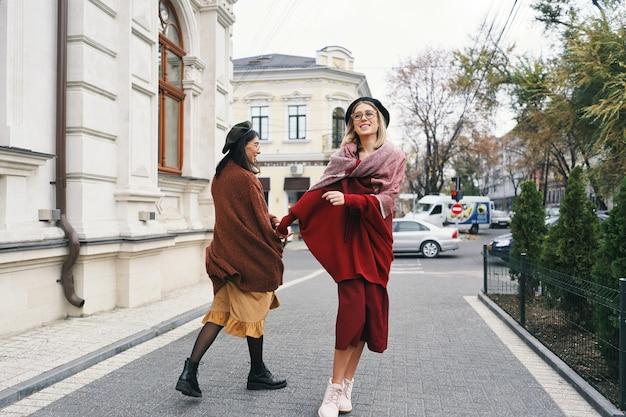 街の通りを歩いている2人のスタイリッシュな女の子との幸せな瞬間。クローズアップの肖像画、楽しい、笑顔、素敵な瞬間、親友、姉妹を持っている面白い楽しい魅力的な若い女性。