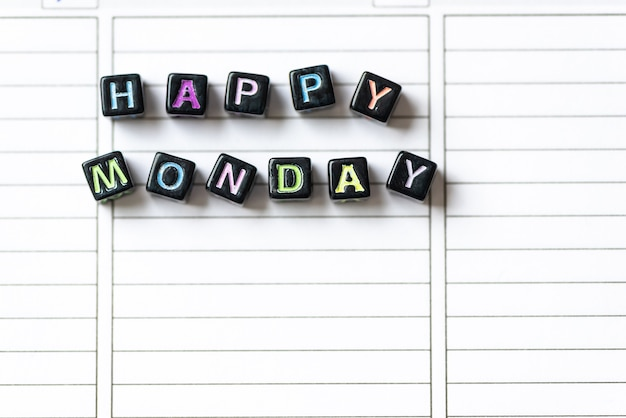 Happy monday of blocks on white page open notebook on desktop