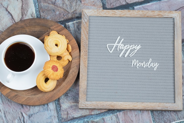 灰色の背景に埋め込まれた幸せな月曜日のポスターと飲み物とクッキーのカップ