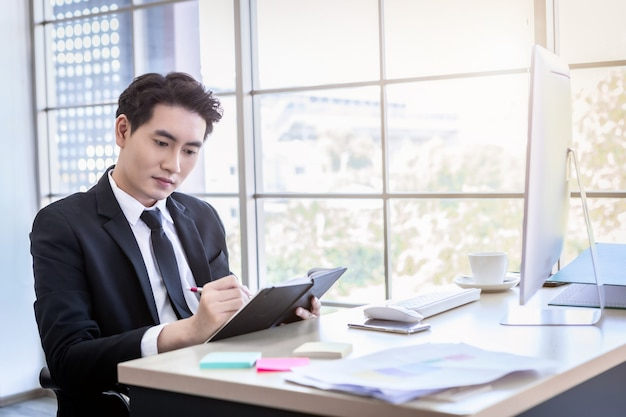 쾌활한 아시아 젊은 사업가의 행복한 분위기는 사무실의 나무 탁자 배경에 있는 노트북과 컴퓨터에서 성공적인 사업 계획을 메모하는 아이디어를 가지고 있습니다.