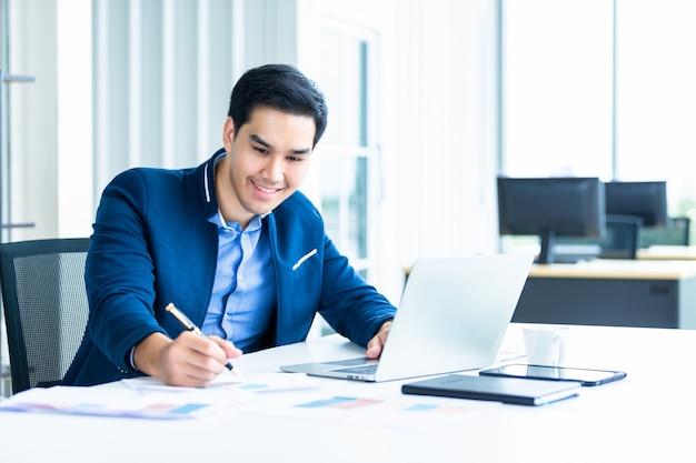 アジアの青年実業家の陽気な幸せな気分は、オフィスで木製のテーブルの上のドキュメント紙とラップトップコンピューターで成功するビジネスプランをメモするアイデアを持っています。