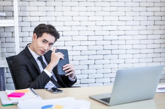 사무실의 나무 테이블 배경에서 테이블과 노트북 컴퓨터를 가지고 일하는 쾌활한 성공적인 아시아 젊은 사업가
