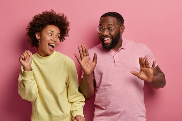 행복한 분위기와 엔터테인먼트. 긍정적 인 유머러스 한 아프리카 계 미국인 부부는 팔을 들고 춤을 추고, 음악을 듣고, 따라 노래하고, 활발하게 움직입니다.