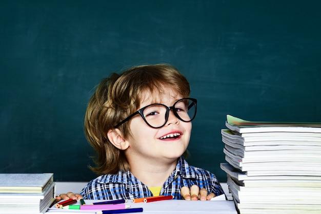 학교에서 넓게 웃는 행복한 기분. 녹색 칠판에 대한 학교 애들. 어려운 시험. 작은