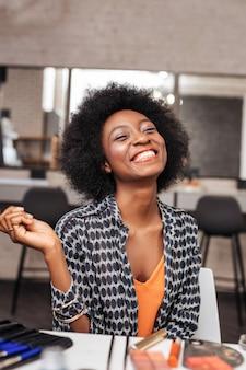 幸せな気分。オレンジ色のトップスを着た幸せそうな笑顔の女性
