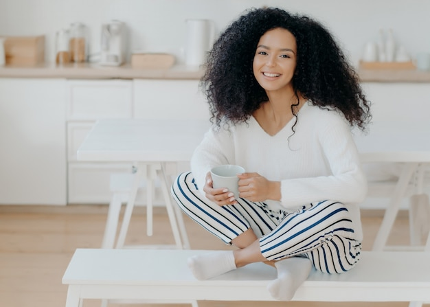 Happy morning concept. photo of cheerful curly african american woman sits in lotus pose at white bench, sips tasty aromatic drink, feels relaxed, poses against kitchen interior, smiles broadly