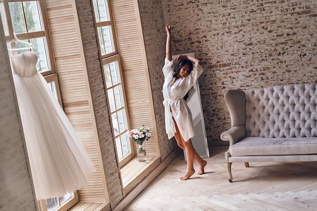 幸せな朝。目を閉じて、窓の近くでストレッチしながら笑顔を保つシルクのバスローブを着た美しい若い女性の全長