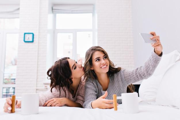 Счастливое утро двух радостных привлекательных девушек, делающих селфи на белой кровати. довольно молодые женщины веселятся вместе, улыбаются, отдыхают, пьют кофе, друзья.