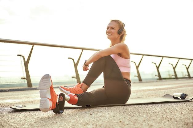 Счастливое утро позитивная женщина-спортсмен-инвалид с протезом ноги в наушниках делает упражнения йоги