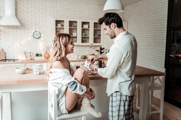 행복한 아침. 그녀의 남편과 아침을 보내는 동안 의자에 앉아 두꺼운 양말을 입고 젊은 장발 예쁜 여자 미소