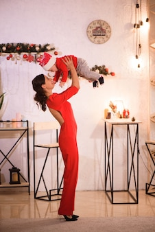 Happy mother and adorable baby in santa hat celebrate christmas.