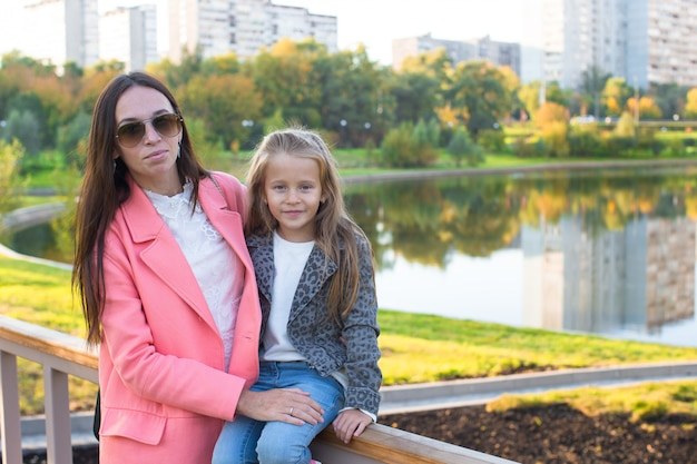 Happy mother and adorable girl enjoying warm autumn day