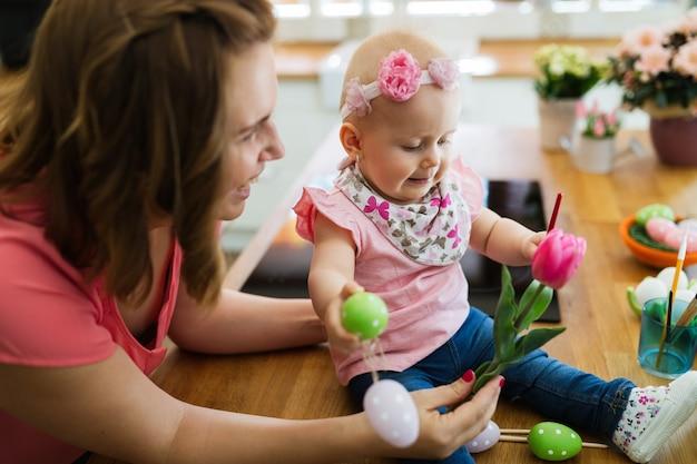 Счастливая мать и ребенок, делая украшение с букетом тюльпанов в ведре