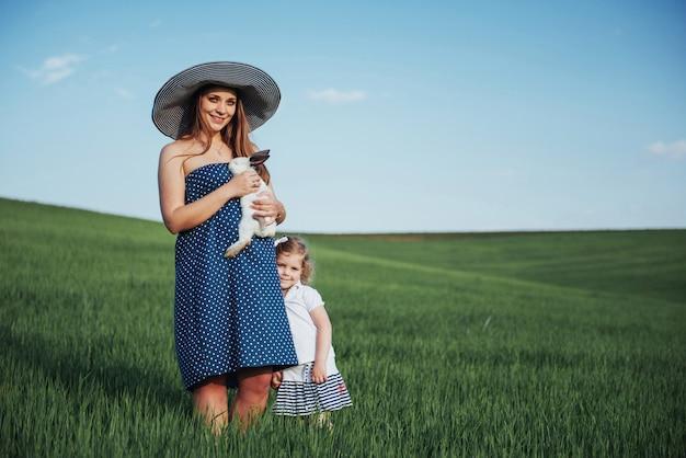 幸せな母親と赤ちゃんのフィールドに手にウサギ