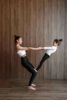 Счастливая мать и ребенок, маленькая девочка, тренируются вместе, поддерживают йогу в тренажерном зале