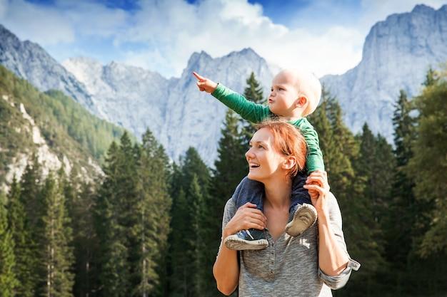 山でのトレッキングの日に楽しみにして空の家族を指している幸せな母と子