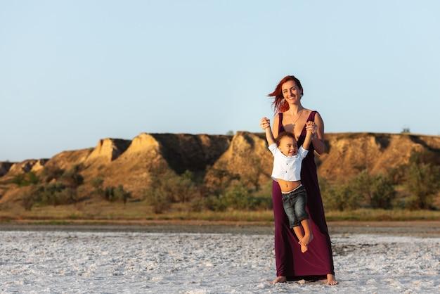 Счастливая мать и ребенок, сын, играющий на пляже