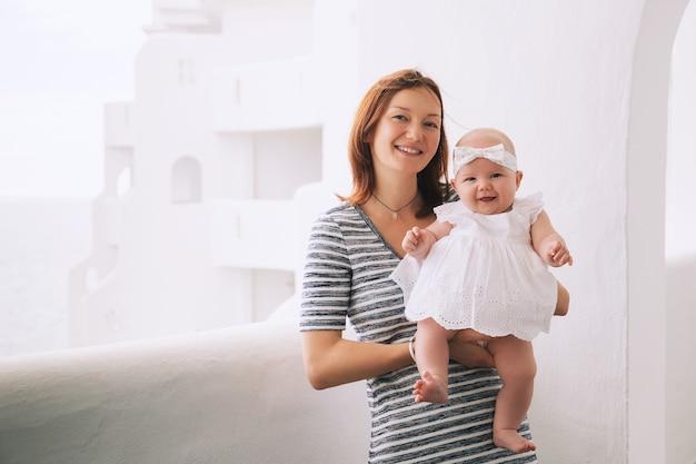 행복한 엄마와 귀여운 5개월 아기 소녀 야외에서 작은 하얀 드레스를 입은 딸과 함께 엄마