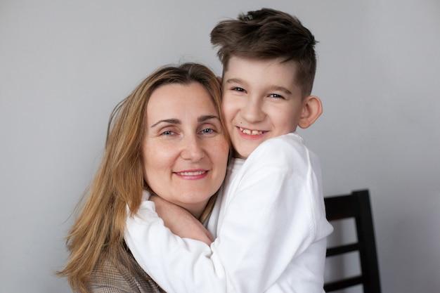 Счастливая мать и милый ребенок дома. портрет улыбающейся мамы, обнимающей сына. концепция счастливого материнства