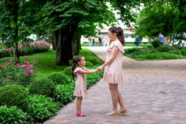 5〜6歳の幸せな母と娘が夏に公園を散歩し、母が娘と話す、幸せな家族の概念、母と子の関係