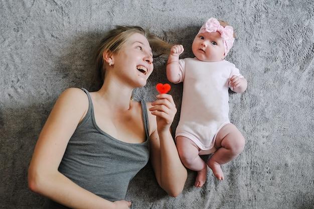 幸せな母と娘。小さな女の子、赤ちゃん、新生児、お母さんは、おもちゃで遊んで、表面のベッドに横たわっています。写真撮影は4-5ヶ月。フラットレイ。上面図。