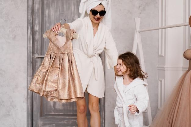 Счастливая мать и дочь выбирают платье в гардеробе. на матери белый халат. они идут на вечеринку.