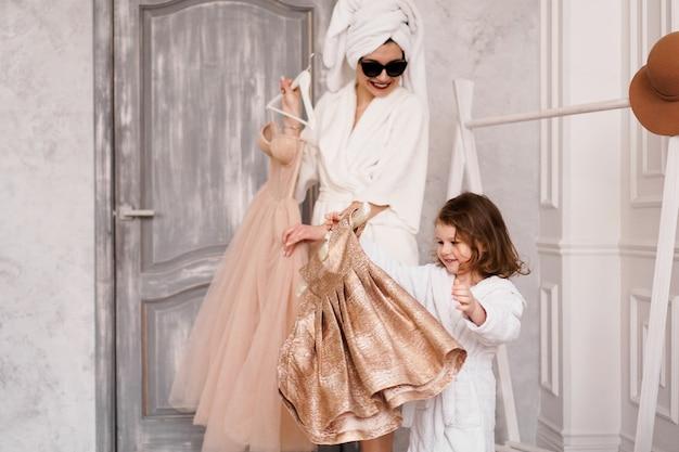 행복한 엄마와 딸이 옷장에서 드레스를 선택하고 있습니다. 어머니는 흰색 목욕 가운을 입고 있습니다. 그들은 파티에 갈 것입니다.