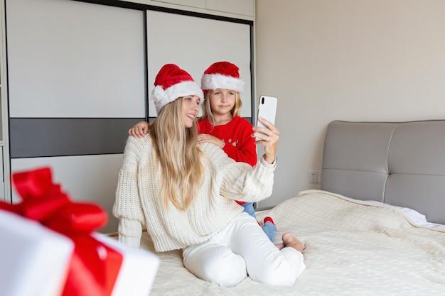 화상 통화와 함께 친구를 축하하는 행복 한 엄마와 딸. 크리스마스 온라인 휴일 축하