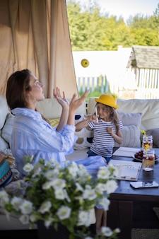 幸せな母と娘は夏の屋外テラスで新鮮なフルーツカクテルとガラスのチャリンという音を応援します