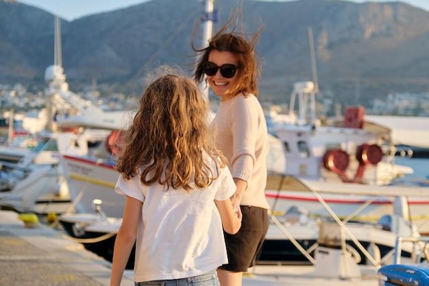 幸せな母と娘の子供が海辺に沿って手をつないで一緒に歩いています。ヨットのマリーナ、海に沈む夕日、風光明媚な山々の背景。家族、愛、旅行、ライフスタイル、休暇の概念