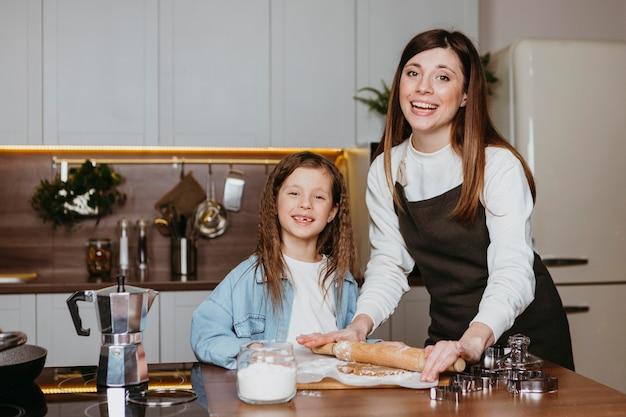 幸せな母と娘がキッチンで料理