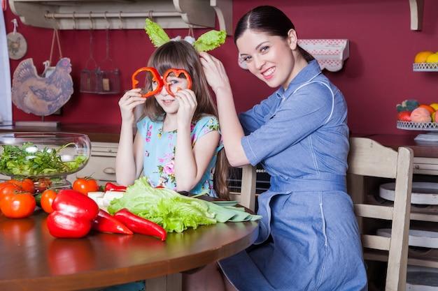 Счастливая мать и дочь любят готовить и вместе готовить здоровую еду на своей кухне. они вместе готовят овощной салат и веселятся. мама позаботится о дочери и научится готовить.