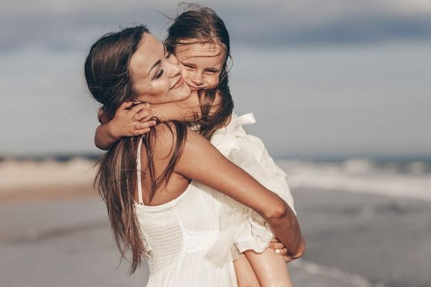 幸せな母と娘のビーチで晴れた日を楽しむ