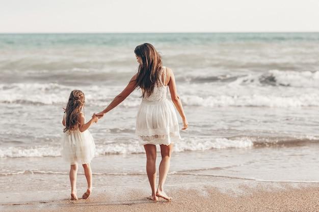 Счастливая мать и дочь, наслаждаясь солнечный день на пляже